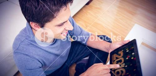 Composite image of overhead view of man using digital tablet in living room