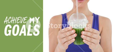 Composite image of woman showing green juice in goblet