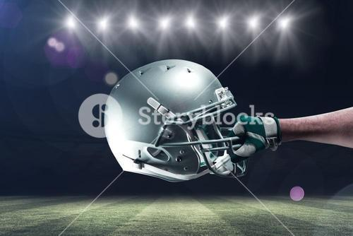 Composite image of cropped hand of sportsman holding helmet