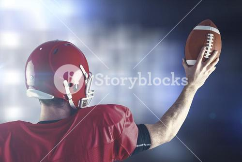 Composite image of rear view of american football player holding up football