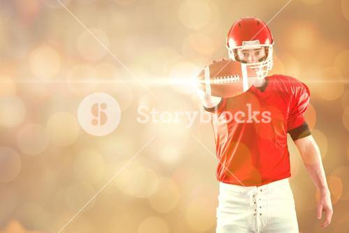 Composite image of portrait of american football player showing football to camera