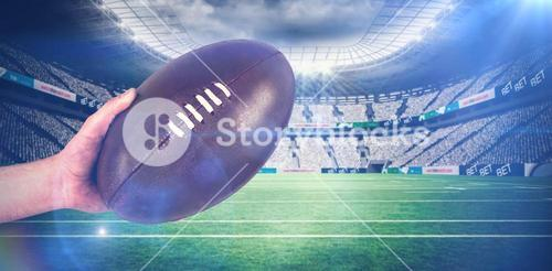 Composite image of rugby player handing a rugby ball