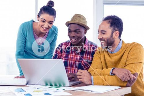 Happy business people working on laptop