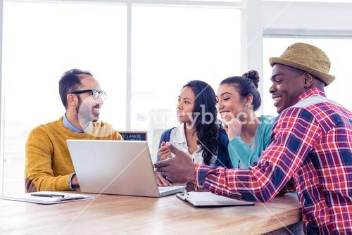 Business people discussing on laptop