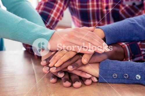 Business people with stacked hands on desk