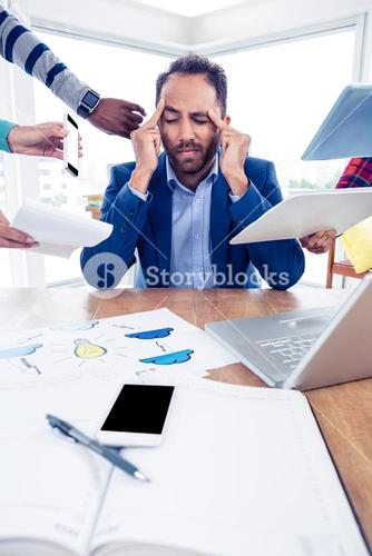 Stressful businessman with head in hands at creative office