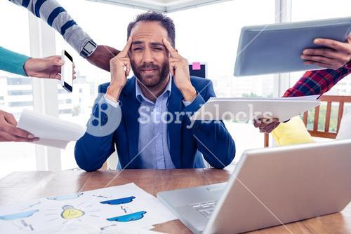Stressful businessman by colleagues in creative office