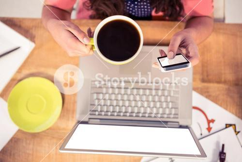 Cropped image of businesswoman using phone while holding coffee cup