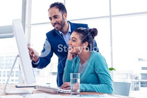 Happy businessman pointing and explaining to coworker over PC