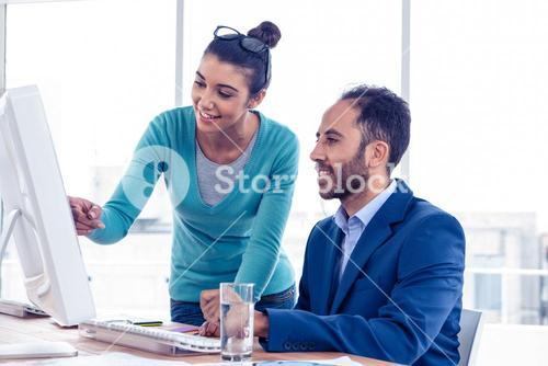 Happy businesswoman explaining to coworker over PC