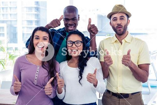 Portrait of creative business people with thumbs up