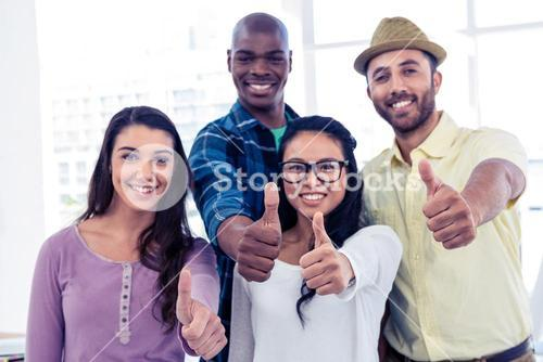 Portrait of creative business people showing thumbs up