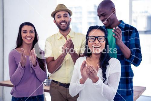 Portrait of businesswoman applauding with team