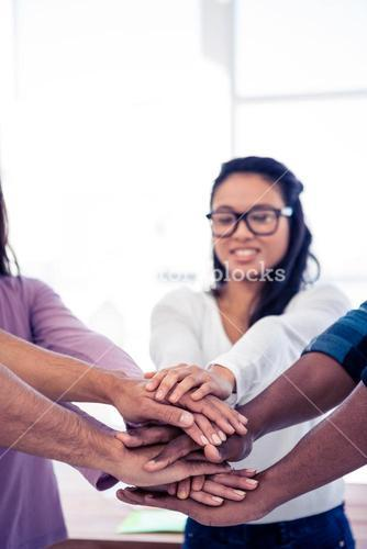 Businesswoman stacking hands with team