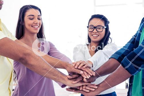Businesswomen stacking hands with team