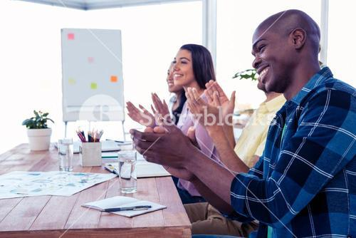 Cheerful businessman applauding in conference room