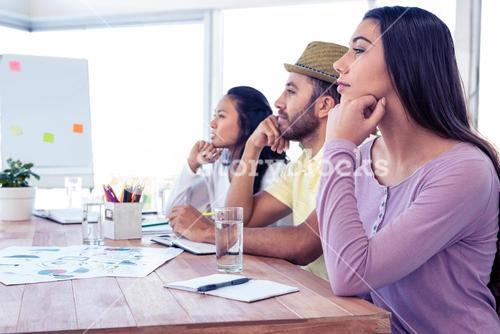 Colleagues day dreaming while sitting in conference room