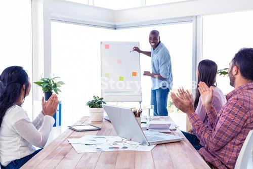 Cheerful businessman giving presentation while team applauding in office