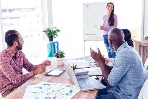 Business people applauding for female colleague