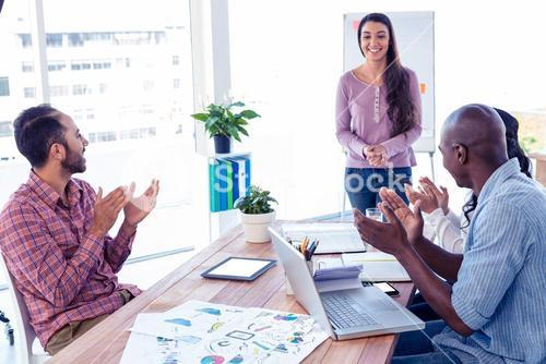 Business people applauding for female coworker