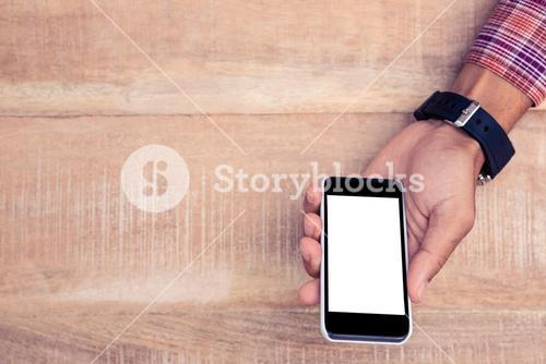 Person holding smart phone on desk