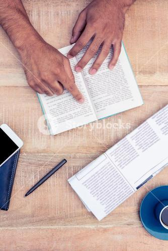 Man reading book on table