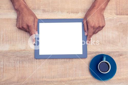 Hand holding on digital tablet over table by coffee