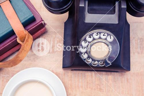 Old landline telephone with diaries and coffee