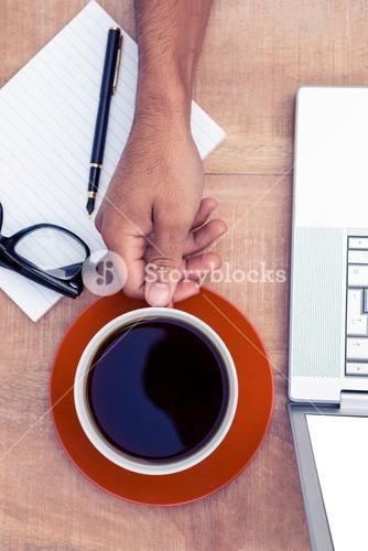 Businessman having coffee on desk in office