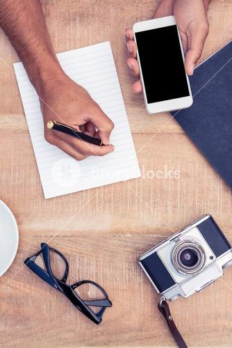 Cropped image of man writing on notepad while holding smart phone