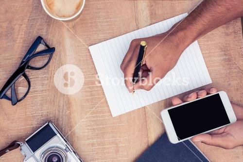 Cropped image of businessman writing on notepad
