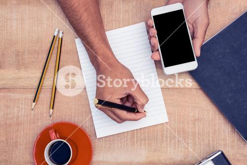 Overhead view of businessman hand holding smart phone while writing