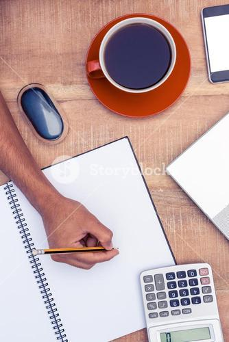 Businessman writing on notebook by coffee at desk