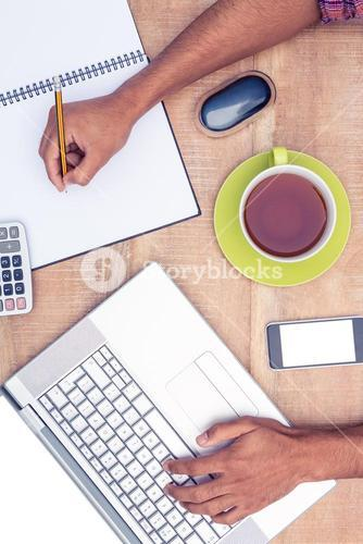 Businessman working on laptop while writing on book