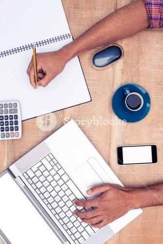 Overhead view of businessman writing on book while working on laptop