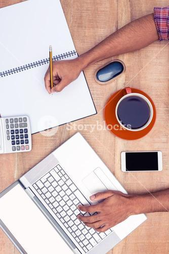 Cropped businessman working on laptop while writing on book