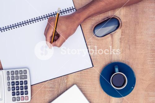 Cropped image of businessman writing on notebook by coffee at desk