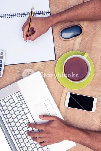 Overhead view of businessman working on laptop