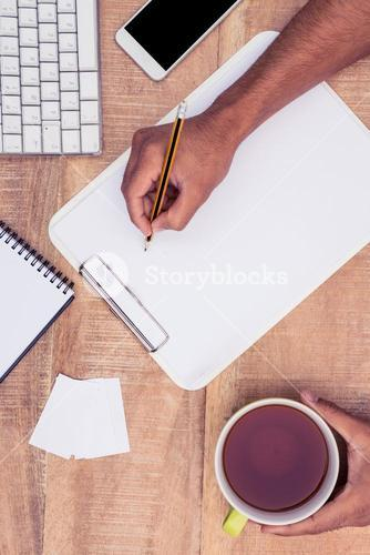 Cropped image of businessman writing on notebook