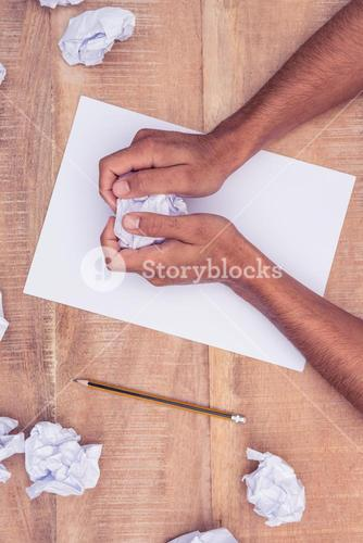 Businessman by notepad making paper balls at desk