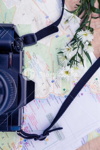 Overhead view of digital camera and map and flowers