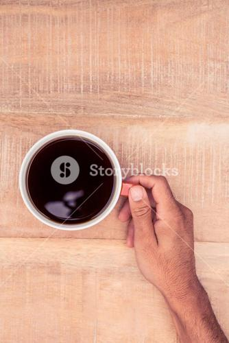Businessman holding black coffee on desk