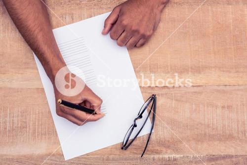 Businessman writing on paper at desk