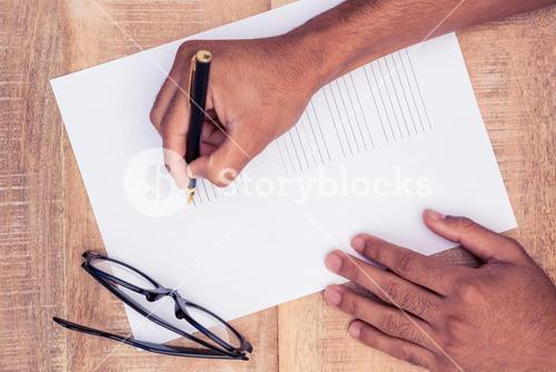 Cropped hand of businessman writing on paper