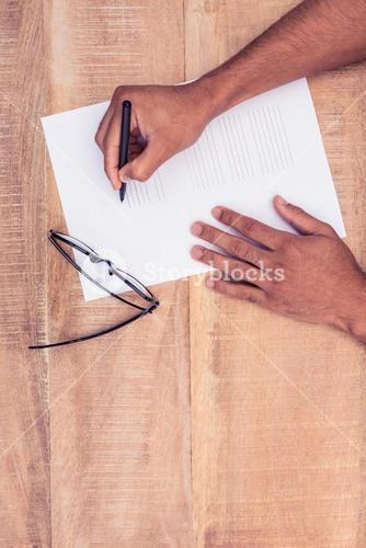 Businessman writing on paper by eye glasses at desk
