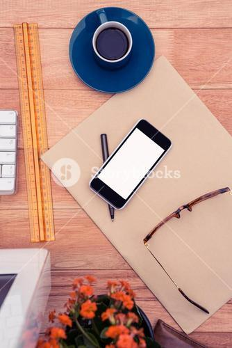 Smartphone by eye glasses on paper by coffee cup at desk