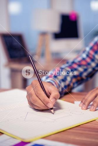 Cropped hand of businessman drawing house in book