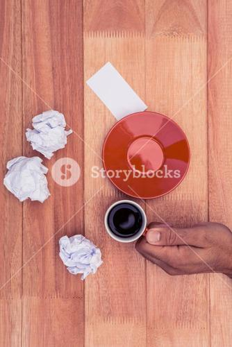 Hand holding coffee cup by crumbled paper and saucer on desk