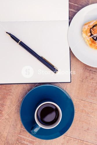 High angle view of pen on notepad by food and coffee at table