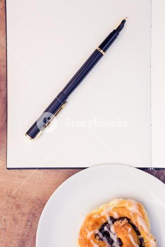 Pen and notepad by sweet food in plate